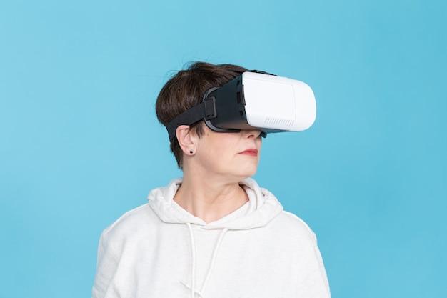 Sourire femme heureuse acquérir de l'expérience à l'aide de lunettes casque vr de réalité virtuelle sur mur bleu