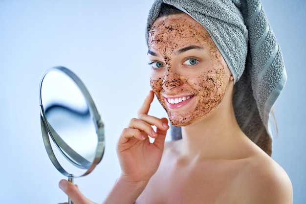 Sourire, femme heureuse, dans, serviette bain, à, figure naturelle, masque gommage café, après, douche