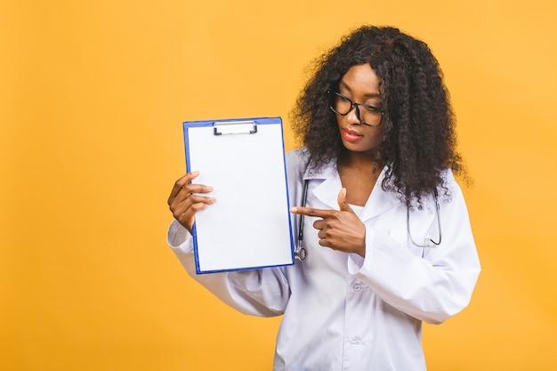 Sourire femme médecin afro-américaine en blouse blanche avec presse-papiers et stéthoscope
