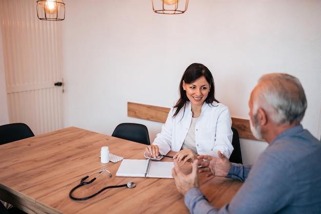 Sourire de femme médecin lors d'une visite à domicile, écouter et parler à un patient âgé.