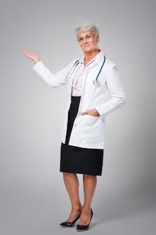 Sourire femme médecin pointant sur l'espace de copie