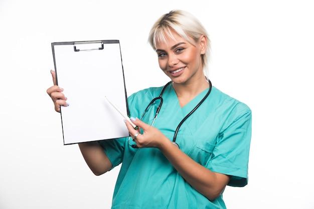 Sourire de femme médecin pointant un presse-papiers avec un stylo sur une surface blanche