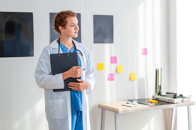 Sourire de femme médecin possédant et portant un stéthoscope sur la chambre d'hôpital.