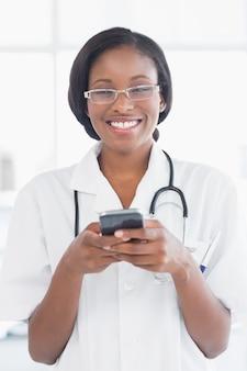 Sourire femme médecin tenant un téléphone portable à l'hôpital