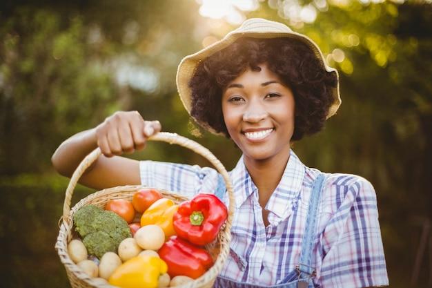 Sourire femme montrant un panier de légumes dans le jardin