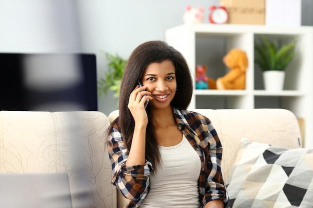 Sourire, femme noire, tenir dans la main, téléphone portable, chez soi
