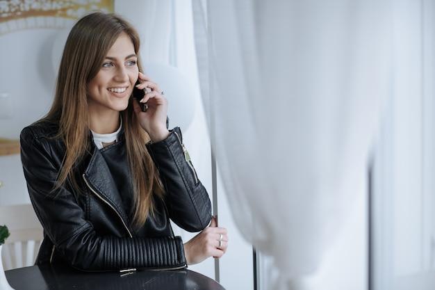 Sourire, femme parle au téléphone