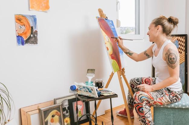 Sourire femme peignant image sur toile