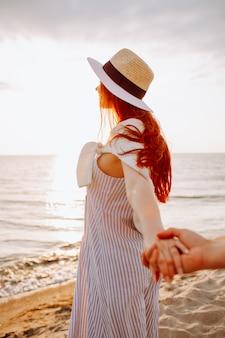 Sourire, femme poil long, dans, a, chapeau, tenue, copains, main, long, vide, océan, plage, sable, à, coucher soleil