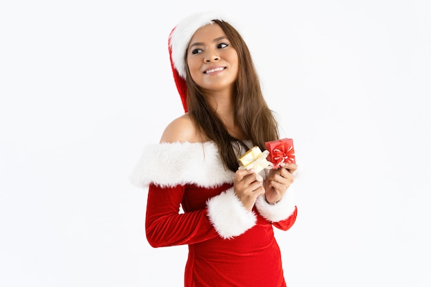 Sourire femme portant bonnet et tenant de petites boîtes-cadeaux