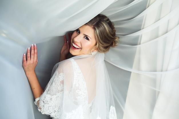 Sourire femme avec des rideaux blancs