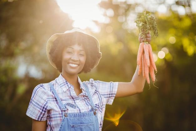 Sourire femme tenant des carottes dans le jardin