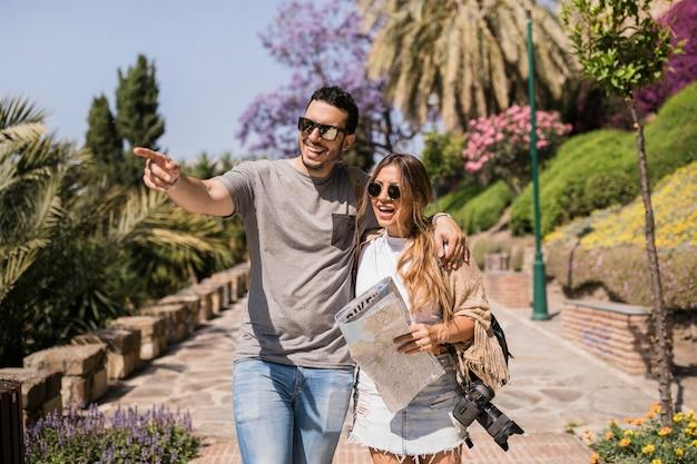 Sourire femme tenant la carte en regardant l'homme pointant le doigt dans le parc
