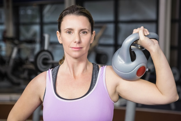 Sourire femme tenant lourd kettlebell a la gym