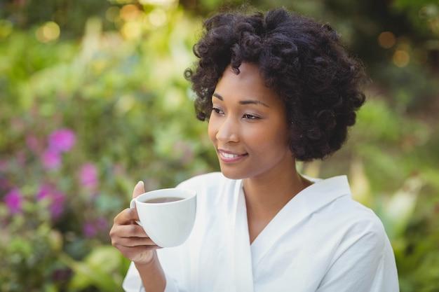 Sourire femme tenant la tasse dans le jardin