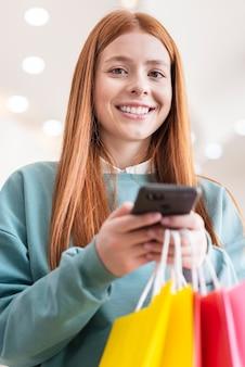 Sourire femme tenant un téléphone et des sacs en papier