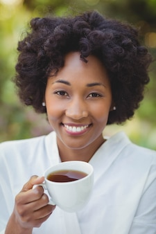 Sourire femme tenant le thé dans le jardin