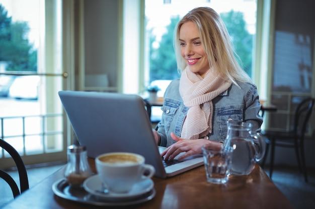 Sourire, femme utilisant un ordinateur portable tout en ayant du café