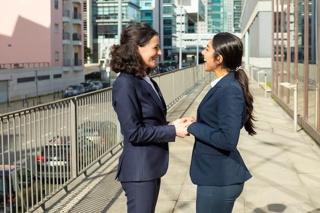 Sourire, femmes affaires, conversation, rue