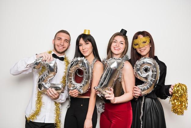 Sourire femmes et homme en tenue de soirée avec numéros de ballons