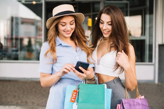 Sourire des femmes regardant l'écran du smartphone