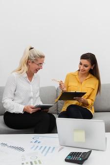 Sourire de femmes tenant une tablette et un presse-papiers