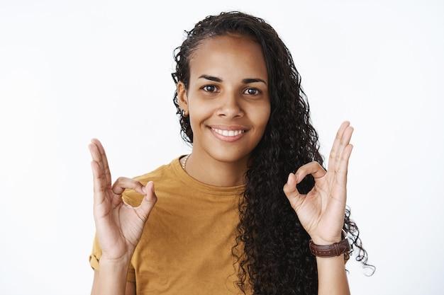 Sourire fille afro-américaine aux cheveux bouclés montrant bien, geste d'approbation