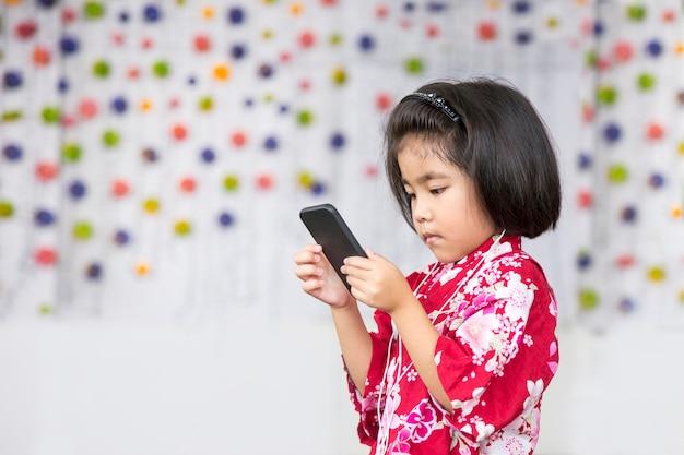 Sourire de fille asiatique avec écouteur et téléphone portable