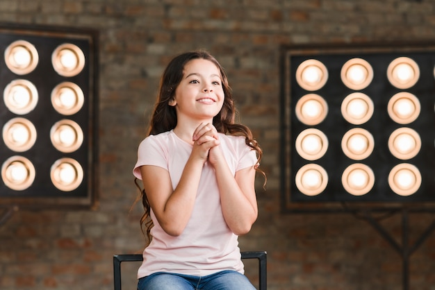 Sourire fille assise contre la lumière de la scène frappant ses mains