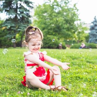 Sourire fille assise sur l'herbe verte jouant avec des bulles transparentes