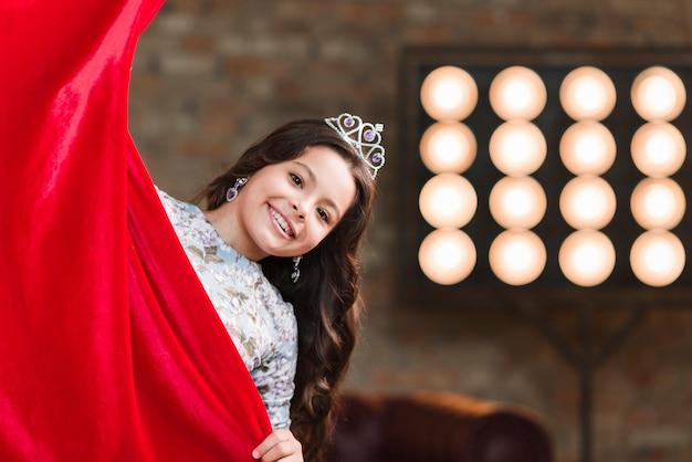 Sourire fille avec une couronne sur sa tête furtivement du rideau rouge