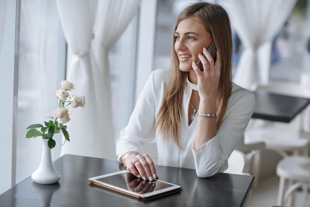 Sourire fille parlant au téléphone et de toucher l'écran d'une tablette