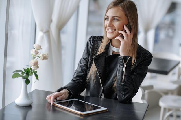 Sourire fille parlant sur le téléphone assis dans un restaurant