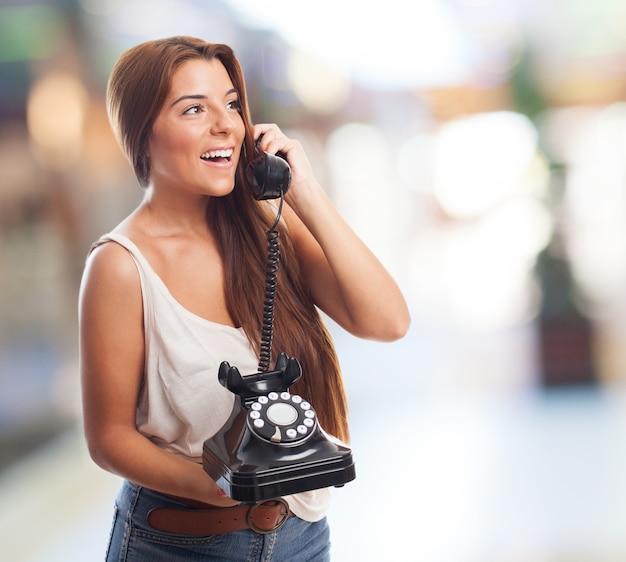 Sourire fille avec un téléphone rotatif