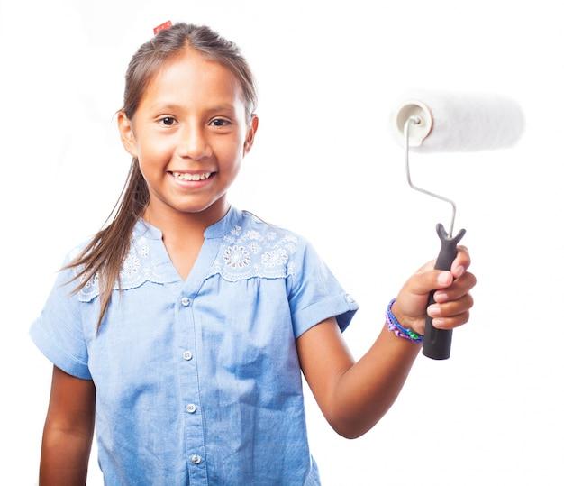 Sourire fille tenant un rouleau de peinture