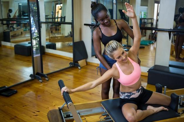 Sourire formateur aidant femme avec pilates sur réformateur
