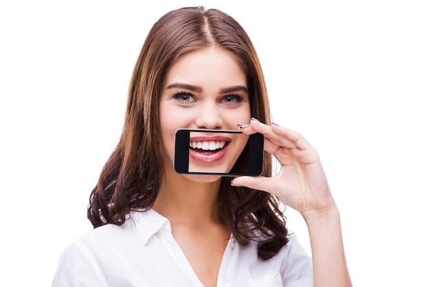 Sourire franc. belles jeunes femmes tenant un téléphone portable contre sa bouche et souriant en se tenant debout sur fond gris
