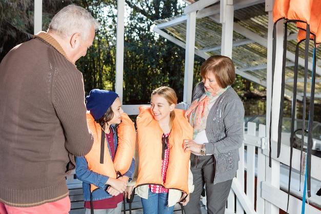 Sourire frères et sœurs portant des gilets de sauvetage avec leurs grands-parents
