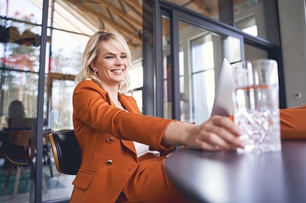 Sourire gai attrayant jeune employé de bureau caucasien atteignant un verre d'eau minérale en cristal