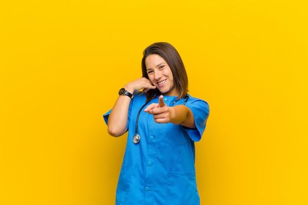 Sourire gaiement et pointer tout en faisant un appel, vous gestes plus tard, parler au téléphone isolé contre le mur jaune