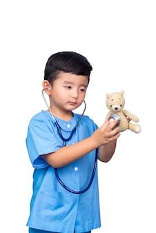 Sourire gamin asiatique en uniforme médical bleu tenant stéthoscope isolé sur blanc avec un tracé de détourage.