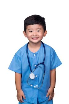 Sourire gamin asiatique en uniforme médical bleu tenant stéthoscope, un tracé de détourage.