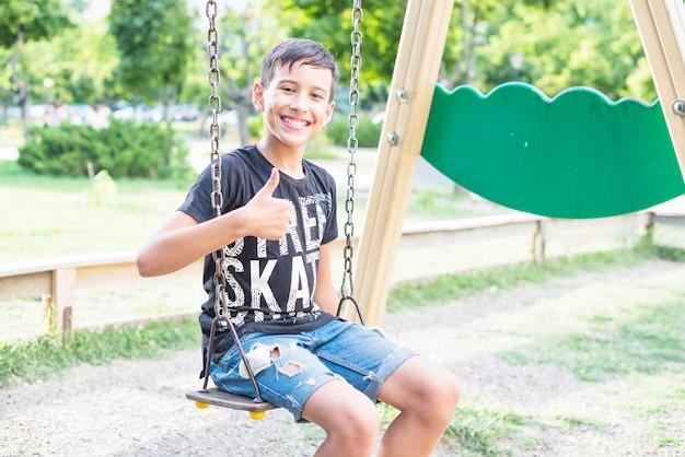 Sourire garçon assis dans la balançoire montrant le pouce en haut signe dans le parc