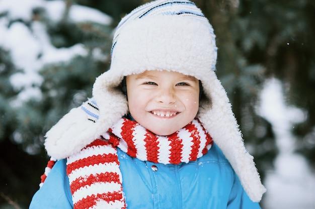Sourire garçon attendant un noël dans le bois,