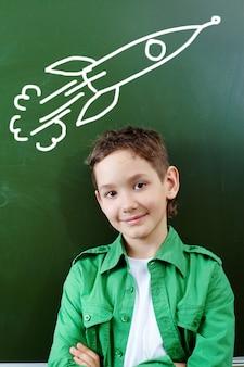 Sourire garçon avec une roquette sur le tableau noir