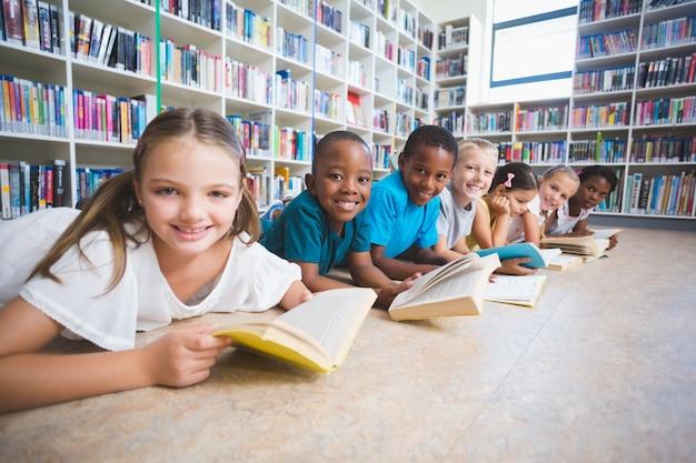 Sourire, gosses école, mensonge plancher, lecture livre, dans, bibliothèque