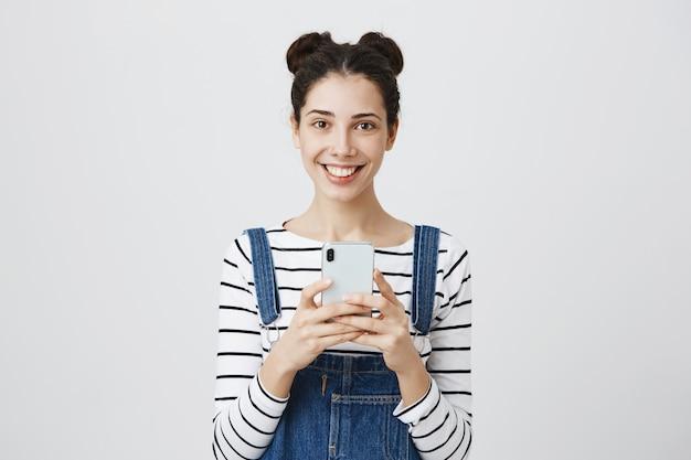 Sourire heureuse adolescente avec smartphone