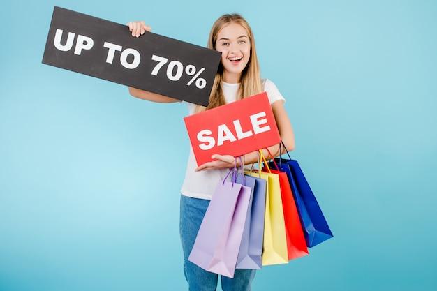 Sourire heureuse belle fille blonde avec vente jusqu'à 70% signe et sacs shopping colorés isolés sur bleu