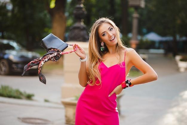 Sourire heureuse femme séduisante élégante en robe d'été sexy rose marchant dans la rue tenant un sac à main élégant