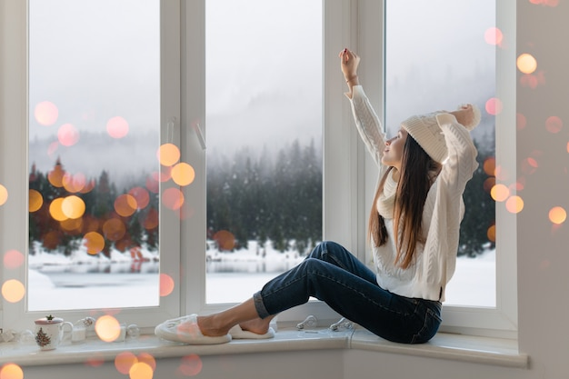 Sourire heureuse jeune femme séduisante en pull tricoté blanc élégant, écharpe et chapeau assis à la maison sur le rebord de la fenêtre à noël s'amuser tenant les mains, vue de fond de forêt d'hiver, lumières bokeh